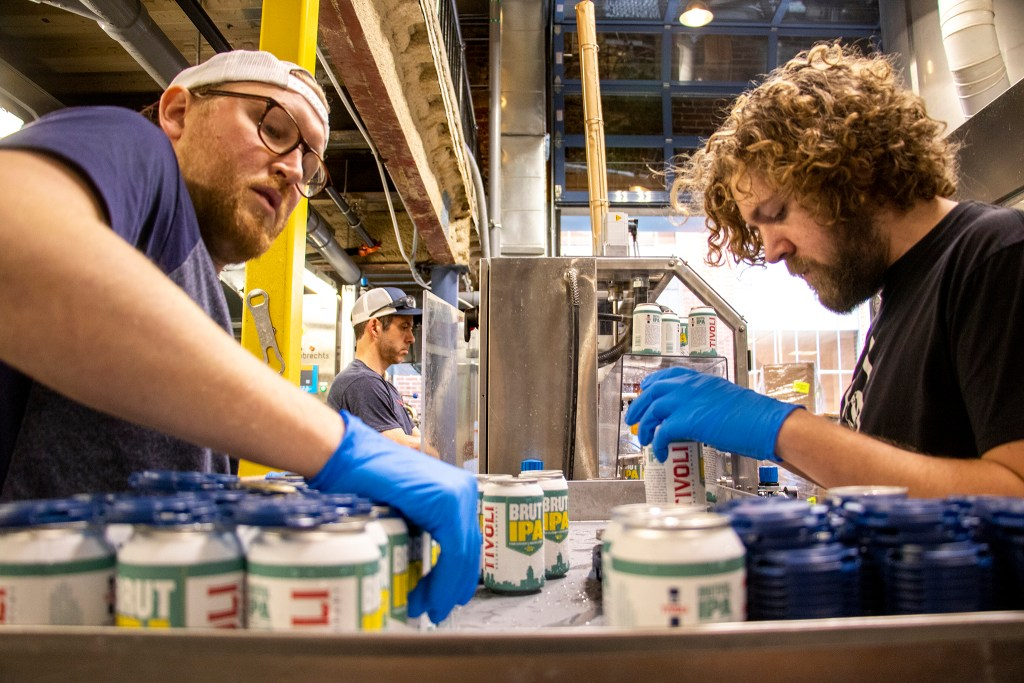 Thomas Zavadal (left to right), Head Brewer Charlie Koller and Jacob Kemple work on a canning assembly line inside Tivoli Brewing Co.'s historic home on the Auraria Campus, March 1, 2019. (Kevin J. Beaty/Denverite)