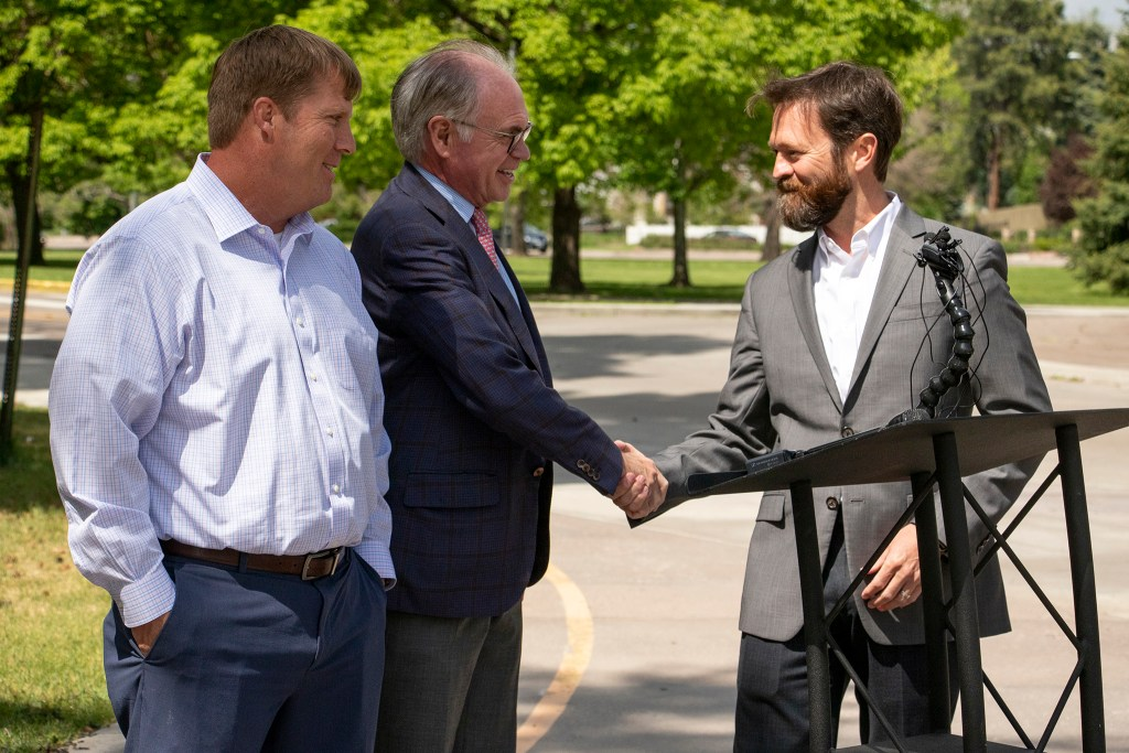 Denver Museum of Nature & Science President and CEO George Sparks (center) thanks Craig Erickson (right) and Dave Rahm after newly-discovered dinosaur fossils arrived at the museum. May 29, 2019. (Kevin J. Beaty/Denverite)