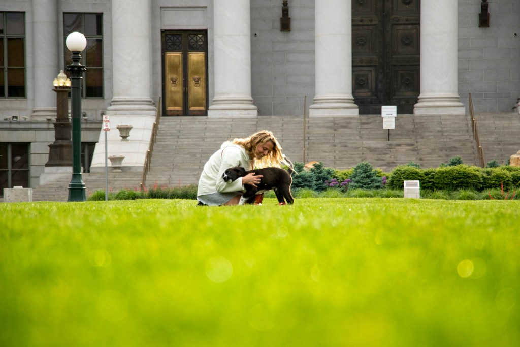 Newly-adopted Archer and his human, Marlena Sacks, frolic in Civic Center Park. May 31, 2019. (Kevin J. Beaty/Denverite)
