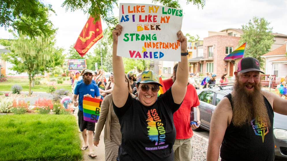 "A marcher holds a sign reading, ""I like my loves like I like my beer,"" during a craft beer Pride parade in Berkeley, June 15, 2019. (Kevin J. Beaty/Denverite)"