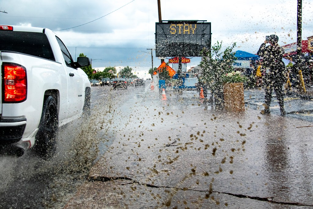 A truck sloshes through a puddle on Federal Boulevard next to the Little Saigon Night Market. June 21, 2019. (Kevin J. Beaty/Denverite)