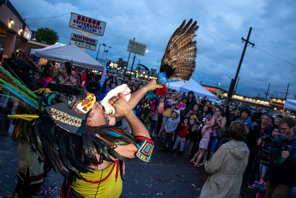 Danny Strange blows into a shell during a ceremony opening the second act at the Little Saigon Night Market. Federal Boulevard, June 21, 2019. (Kevin J. Beaty/Denverite)