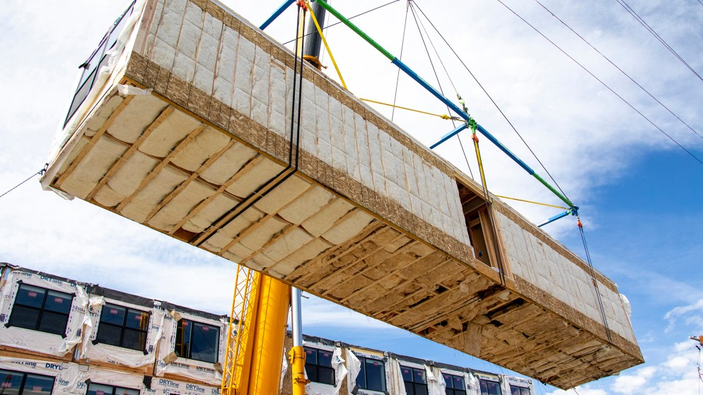 A prefab apartment section is lifted onto the next story of 1775 Federal Blvd., June 25, 2019. (Kevin J. Beaty/Denverite)