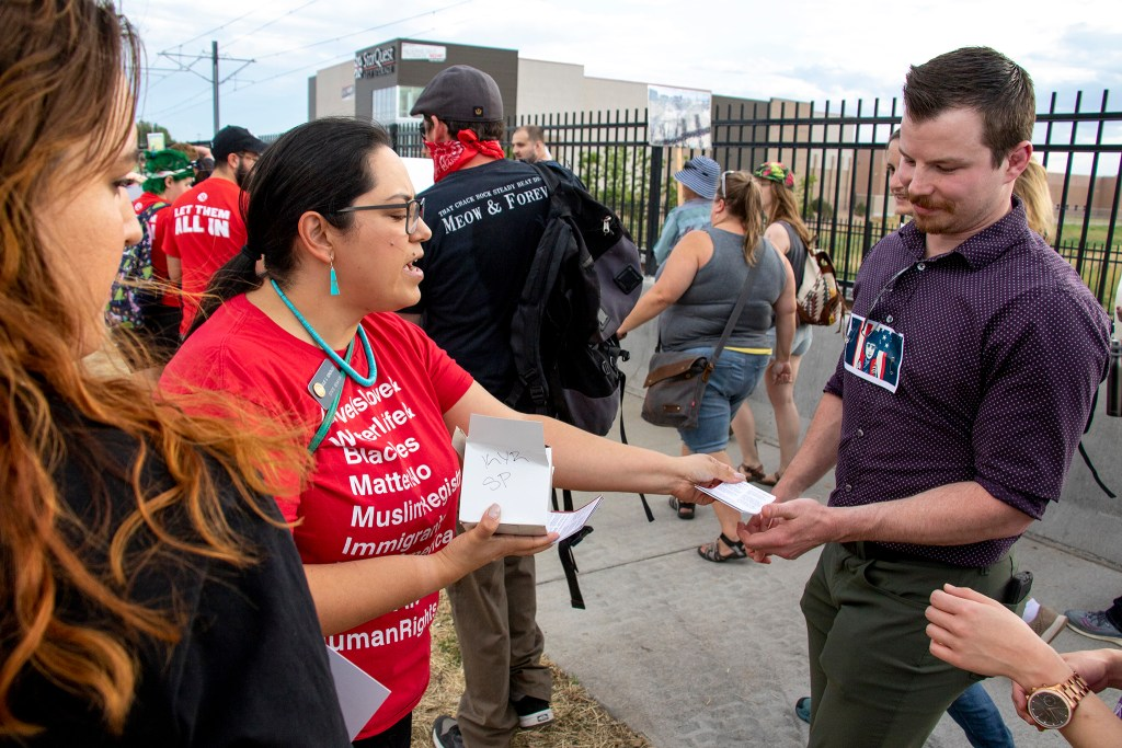 "State Sen. Julie Gonzales hands out ""know your rights"" pamphlets during a march to denounce ICE raids and private immigration jails, June 14, 2019. (Kevin J. Beaty/Denverite)"