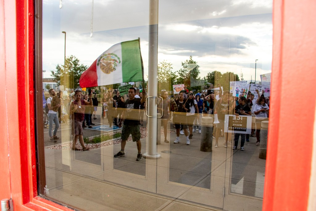 Nacho Perez waves a Mexican flag with a group of protesters gathered on federal property outside of Aurora's private immigration detention facility, June 14, 2019. (Kevin J. Beaty/Denverite)