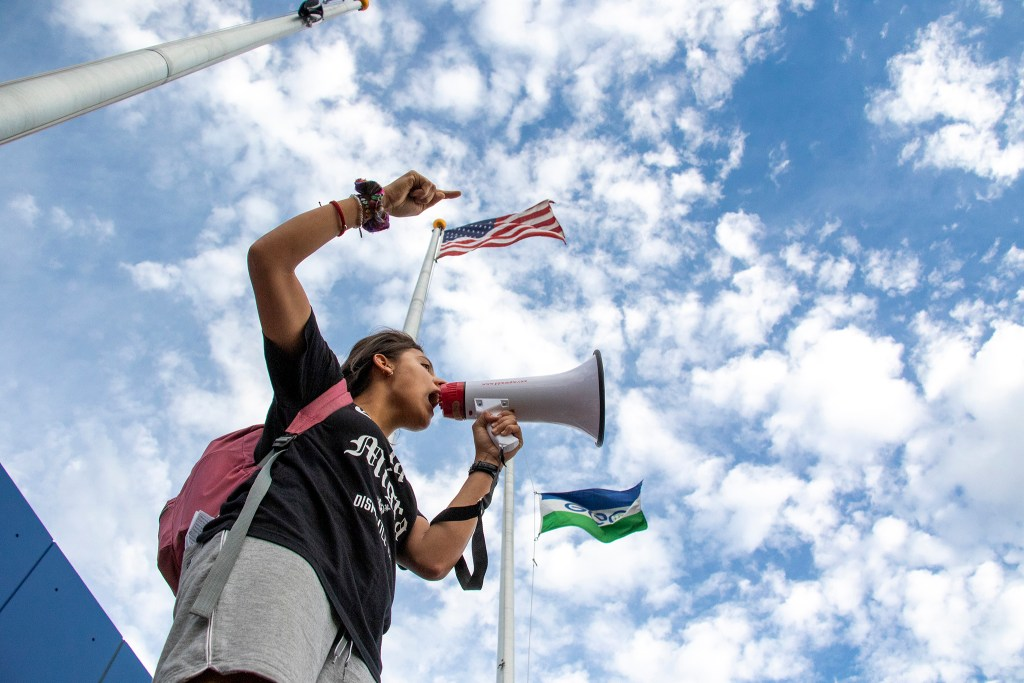 D Garcia pleads with protesters gathered on federal property outside of Aurora's private immigration detention facility to return to the larger protest on the other side of the parcel's line, June 14, 2019. (Kevin J. Beaty/Denverite)