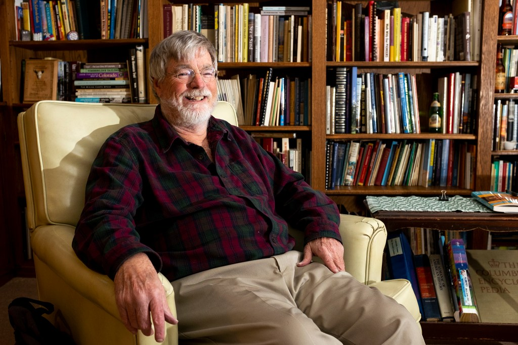 """Historian =, known as """"Dr. Colorado,"""" poses for a portrait in his home library, April 3, 2019. (Kevin J. Beaty/Denverite)"""