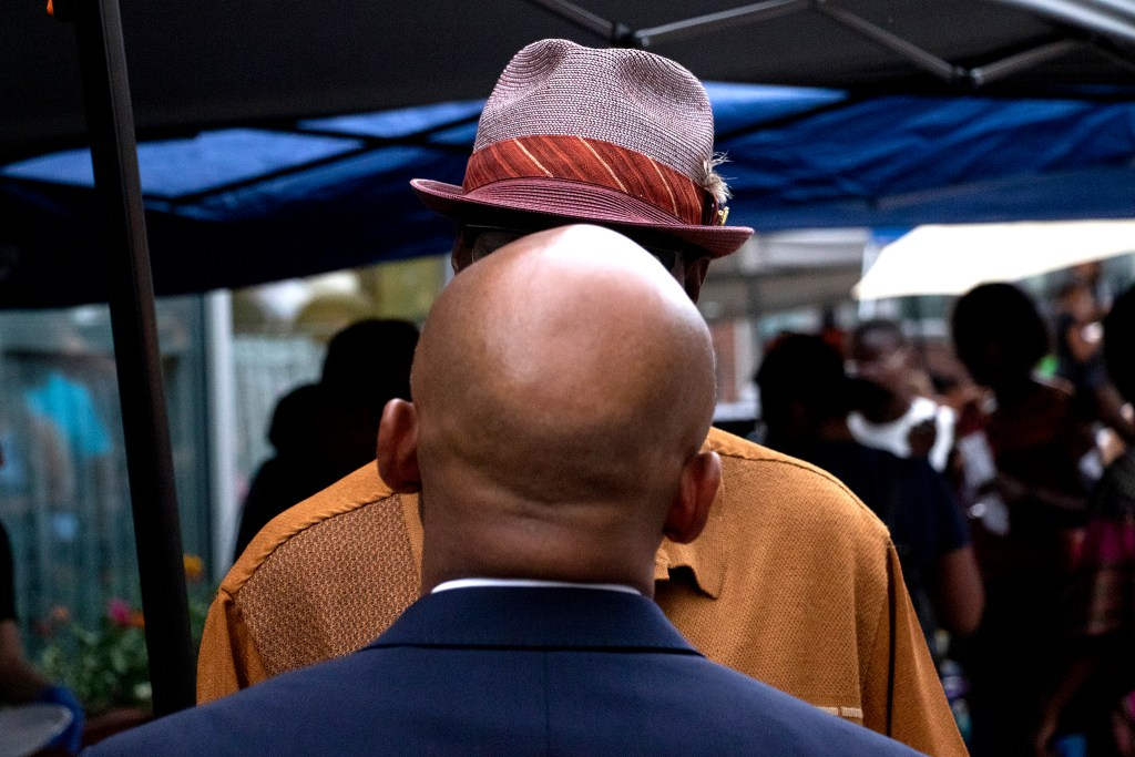 Mayor Michael Hancock speaks to a man in a hat. Welton Street Cafe celebrates 20 years in one location. Five Points, July 30, 2019. (Kevin J. Beaty/Denverite)