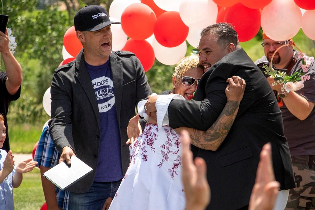"Bryan ""Pastor B"" Sederwall officiates Carlos and LaShawn Serrat's wedding during the Denver Dream Center's Father's Day barbecue at City of Cuernavaca Park, June 15, 2019. (Kevin J. Beaty/Denverite)"