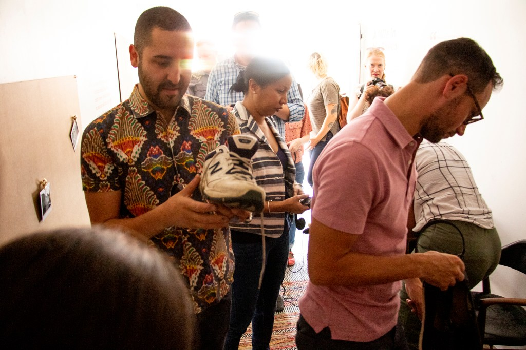"Artist Jonathan Saiz checks out a pair of sneakers, and the story attached to them, inside the Empathy Museum's ""A Mile In My Shoes"" exhibit brought to the 16th Street Mall by the Biennial of the Americas. Aug. 8, 2019. (Kevin J. Beaty/Denverite)"