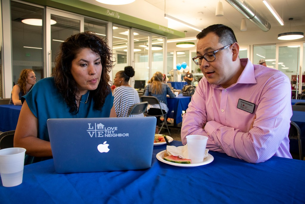 Joseph and Jessica Dominguez plan their housing presentation during a dinner for CrossPurpose's graduates, Aug. 13, 2019. (Kevin J. Beaty/Denverite)