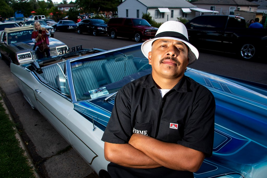 Armando Torres-Arevalo poses for a portrait with his low rider at Barnum Park, after a cruise down Federal Boulevard. Aug. 25, 2019. (Kevin J. Beaty/Denverite)