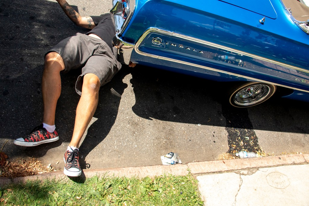 Mio Carr works on his low rider parked by La Raza (or Columbus) Park before a cruise down Federal Boulevard. Aug. 25, 2019. (Kevin J. Beaty/Denverite)