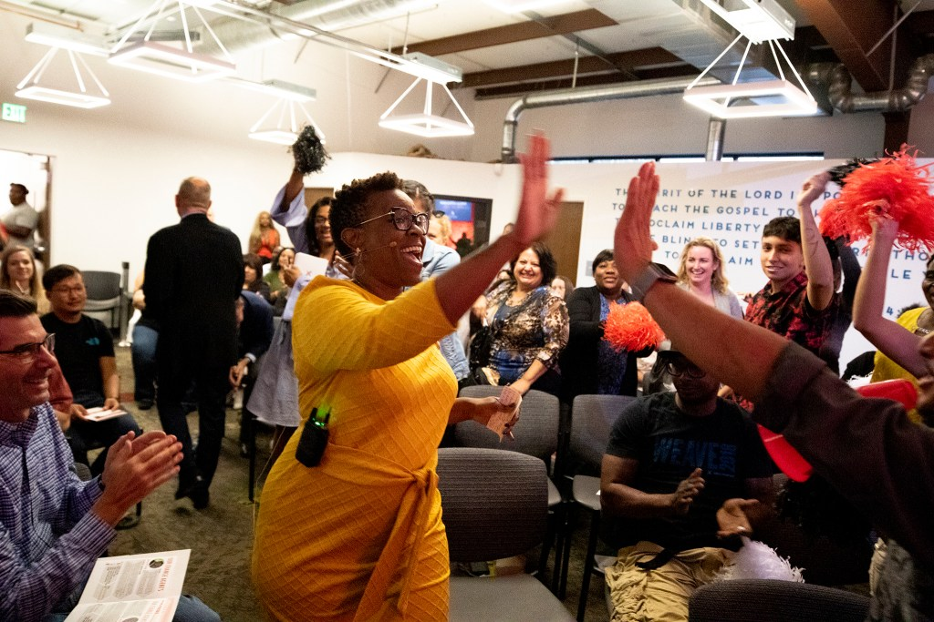 Sheila Littlejohn enters to a warm reception during CrossPurpose's Change Agency pitch night, Sept. 18, 2019. (Kevin J. Beaty/Denverite)
