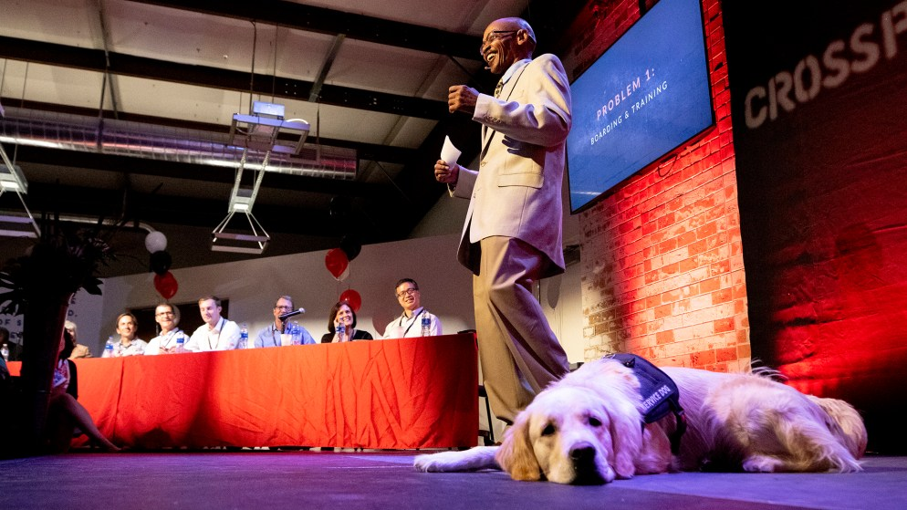 Kenneth Cobbin speaks during CrossPurpose's Change Agency pitch night. Apollo dutifully hangs out on stage. Sept. 18, 2019. (Kevin J. Beaty/Denverite)