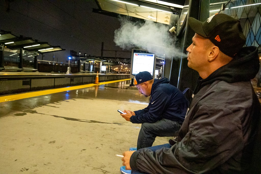 Dominic Ortegon (right) and Shane Romanchuck wait for a train to work at the 38th and Blake RTD station, Oct. 1, 2019. (Kevin J. Beaty/Denverite)
