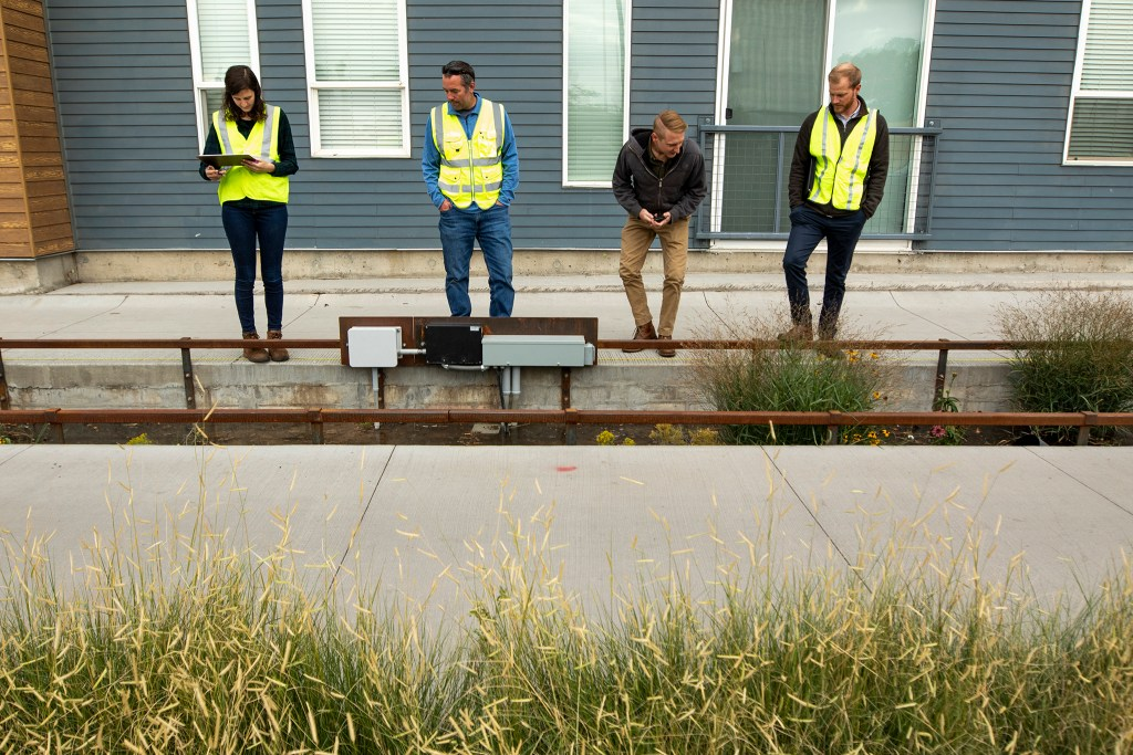 Hailey Rogers (left to right), Colin Bell, Chris Olson and Brandt Schiche watch as a green infrastructure impoundment along Brighton Boulevard is filled with water for testing, Oct. 3, 2019. (Kevin J. Beaty/Denverite)