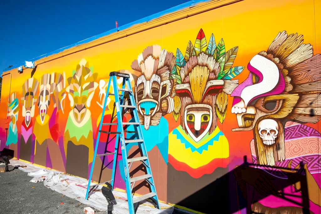 A mural by Güillo Cruz takes shape by the the patio at Raices Brewing Co., Sun Valley, Oct. 26, 2019. (Kevin J. Beaty/Denverite)