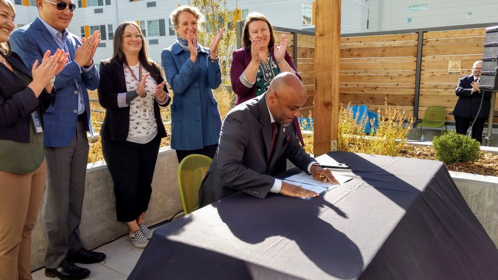 Mayor Michael Hancock signs an executive order establishing Denver's new housing department on Oct. 23, 2019.  (Donna Bryson/Denverite)