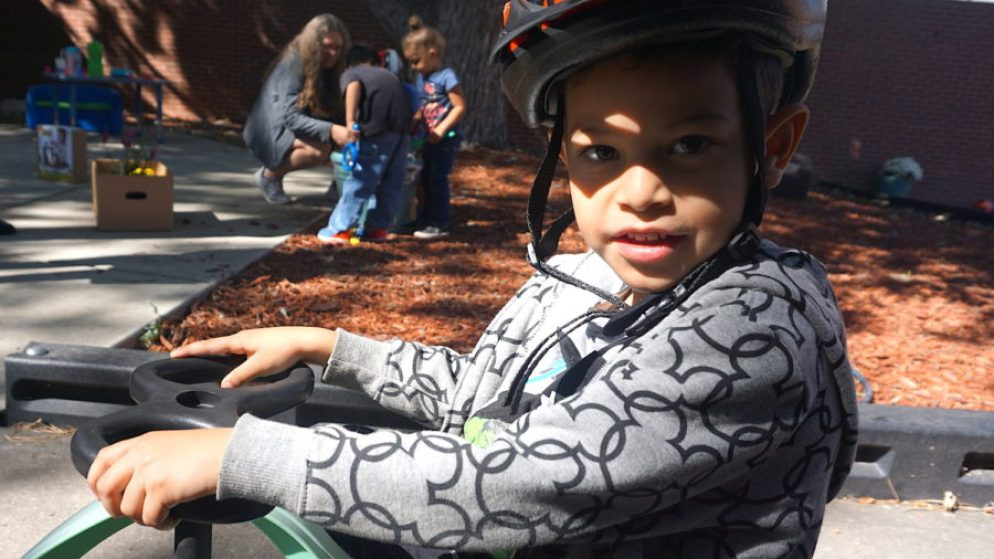 A boy rides a tricycle on the playground of the preschool at Laradon in north Denver. (Alison Roth/Laradon)