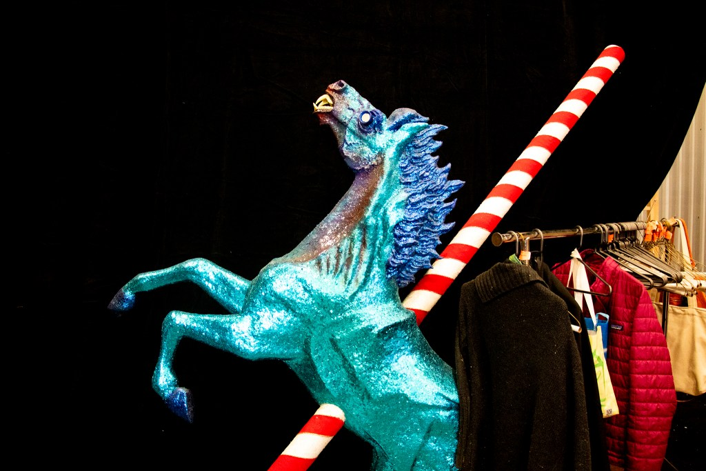 "This scary blue horse appears to have been impaled by a peppermint spear. Lonnie Hanzon's ""Camp Christmas"" is under construction at Stanley Marketplace. Nov. 15, 2019. (Kevin J. Beaty/Denverite)"