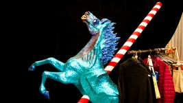 "This scary blue horse appears to have been impaled by a peppermint spear. Lonnie Hanzon's ""Camp Christmas"" under construction at Stanley Marketplace. Nov. 15, 2019. (Kevin J. Beaty/Denverite)"