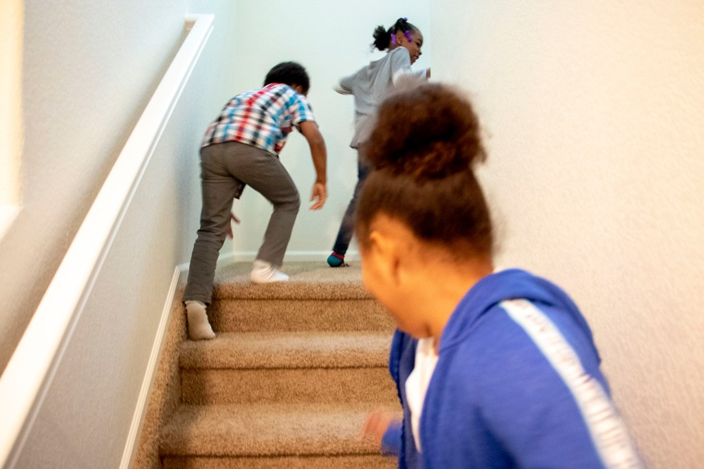 Mele Lavaka's boyfriend's kids, Na'Lonnie, Dedric and KyLani run up the stairs in her new home in Lochbuie, Colorado. Nov. 28, 2019. (Kevin J. Beaty/Denverite)