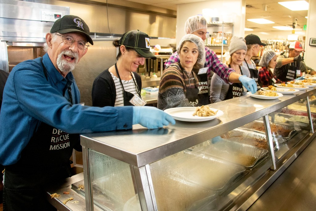 City Councilman Paul Kashmann (left) serves up plates with volunteers for a Thanksgiving feast at the Denver Rescue Mission, Nov. 27, 2019. (Kevin J. Beaty/Denverite)
