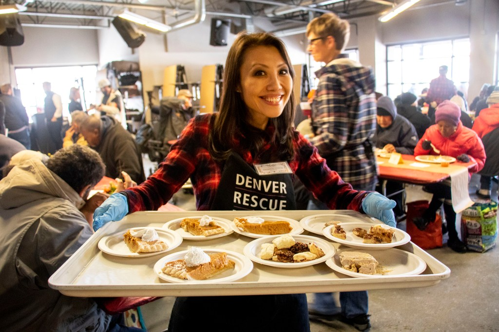Christine Chang holds a tray of pumpkin pie during a Thanksgiving feast at the Denver Rescue Mission, Nov. 27, 2019. (Kevin J. Beaty/Denverite)