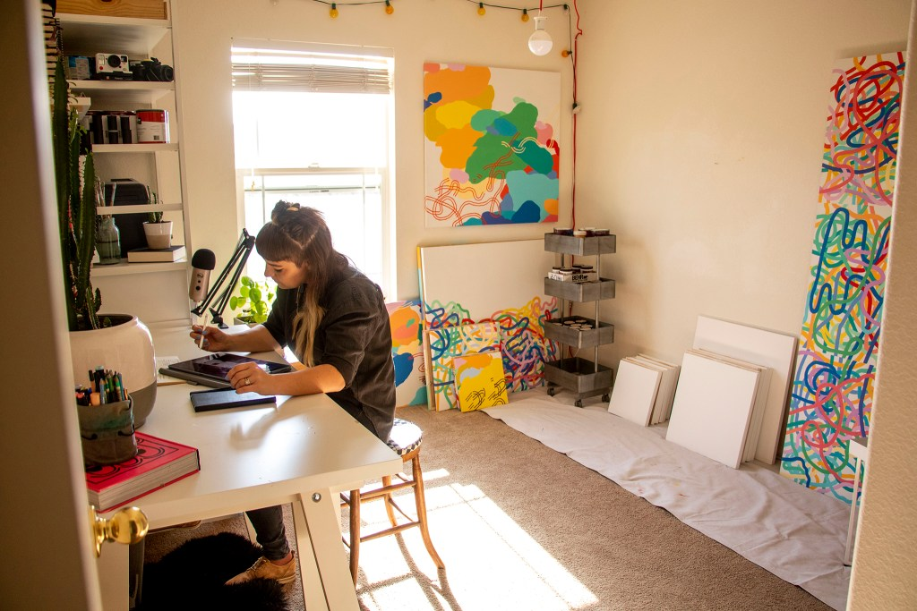 Olive Moya draws on a tablet in her home studio. Dec. 3, 2019. (Kevin J. Beaty/Denverite)