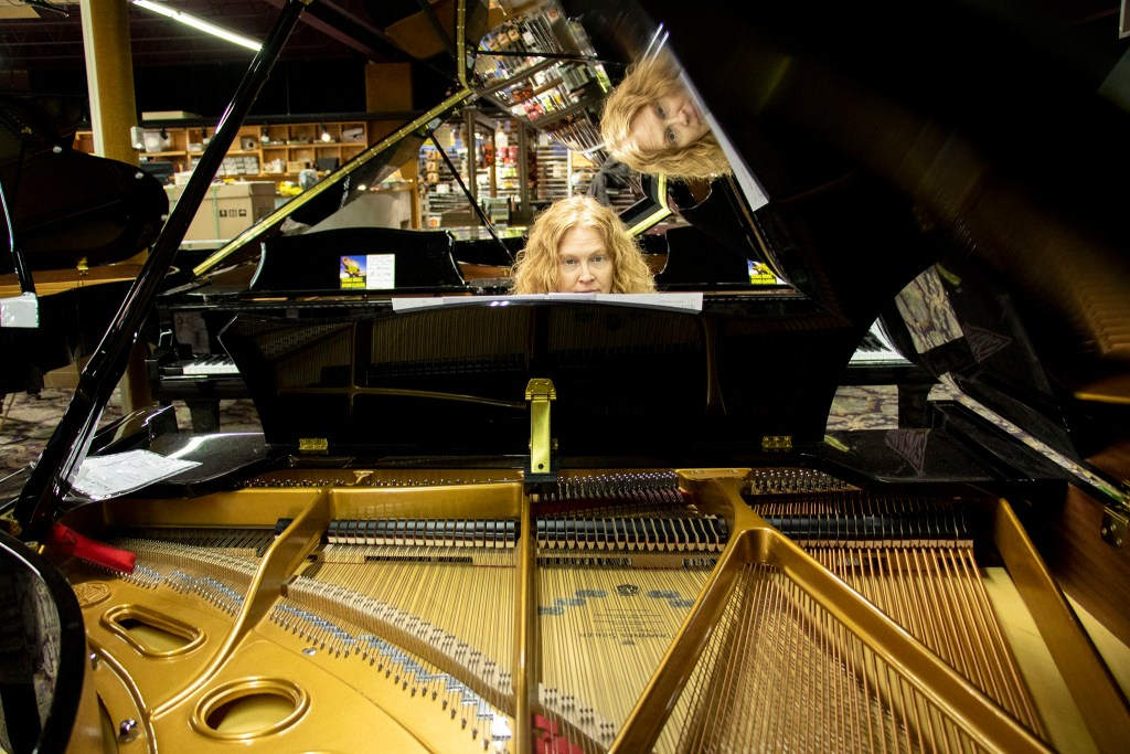Liane Rockley, vice president of Rockley Music Center, plays a grand piano inside her West Colfax Avenue showroom. Lakewood. Dec. 13, 2019. (Kevin J. Beaty/Denverite)