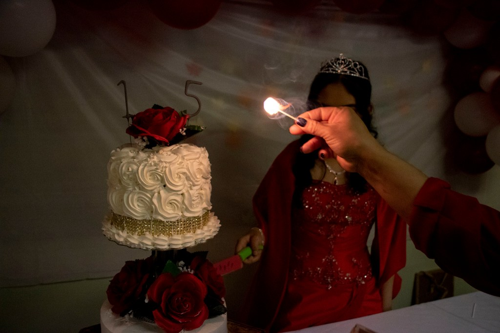Kim Ramos prepares to cut her cake during her quinceañera celebration in the basement of Ministerio Hispano Presbyterian Church, Dec 14, 2019. (Kevin J. Beaty/Denverite)