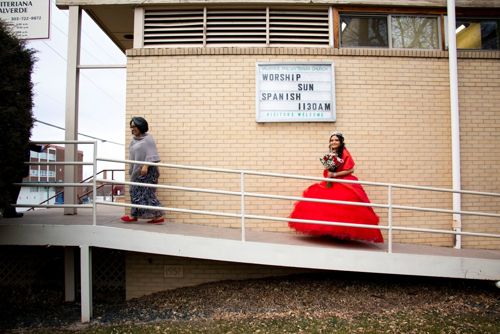 Kim Ramos walks to a side door at Ministerio Hispano Presbyterian Church to make a grand entrance for her  quinceañera, Dec 14, 2019. (Kevin J. Beaty/Denverite)