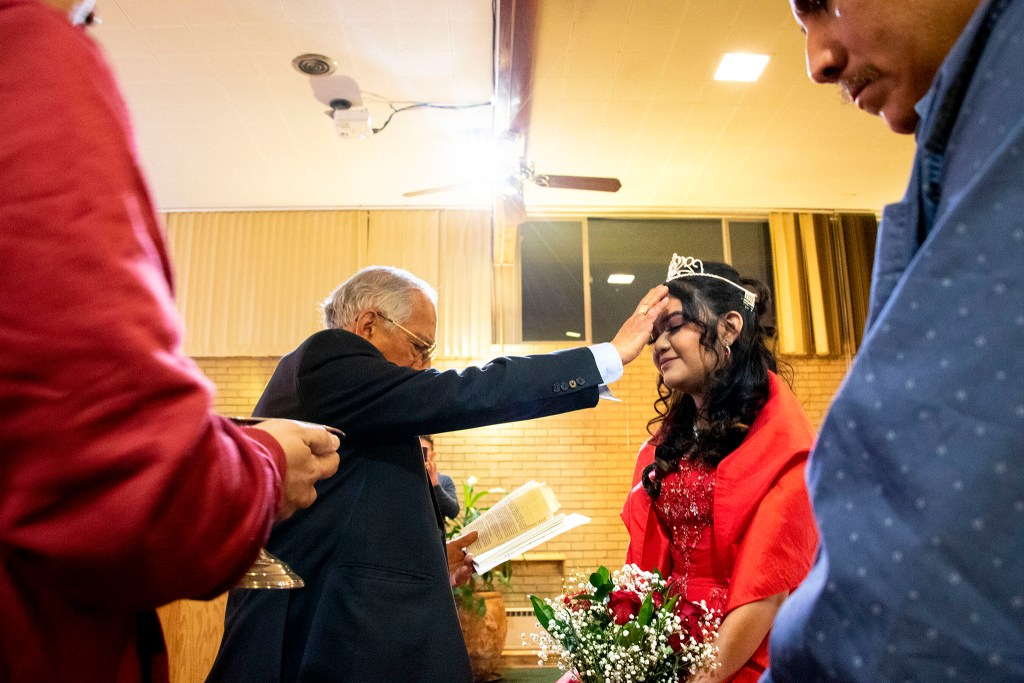 Pastor Rafael Ballares anoints Kim Ramos during her quinceañera ceremony at Ministerio Hispano Presbyterian Church, Dec 14, 2019. (Kevin J. Beaty/Denverite)