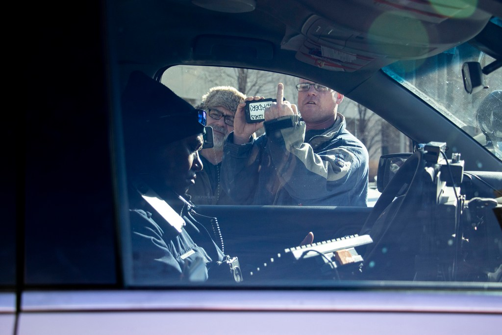 Kyle Shockley (right) yells at a Denver Police officer outside of the Lindsey Flanigan Courthouse. Dec. 18, 2019. (Kevin J. Beaty/Denverite)