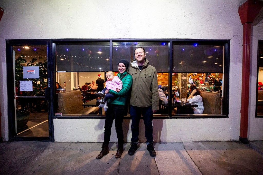 Beau and Lindsay Biskner pose for a portrait with their daughter, Leona, outside of Saigon Bowl on Christmas Eve. Federal Boulevard, Dec. 24, 2019. (Kevin J. Beaty/Denverite)