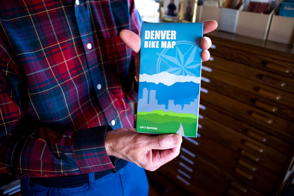 Wesley Brown holds a 2017 Denver Bike Map stored here in his map room. Dec. 16, 2019. (Kevin J. Beaty/Denverite)