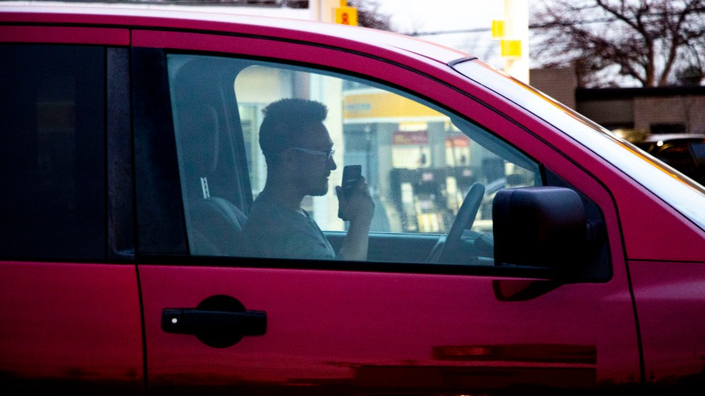 A man talks on a phone in a car at the corner of Federal Boulevard and Florida Avenue, Jan. 16, 2020. (Kevin J. Beaty/Denverite)