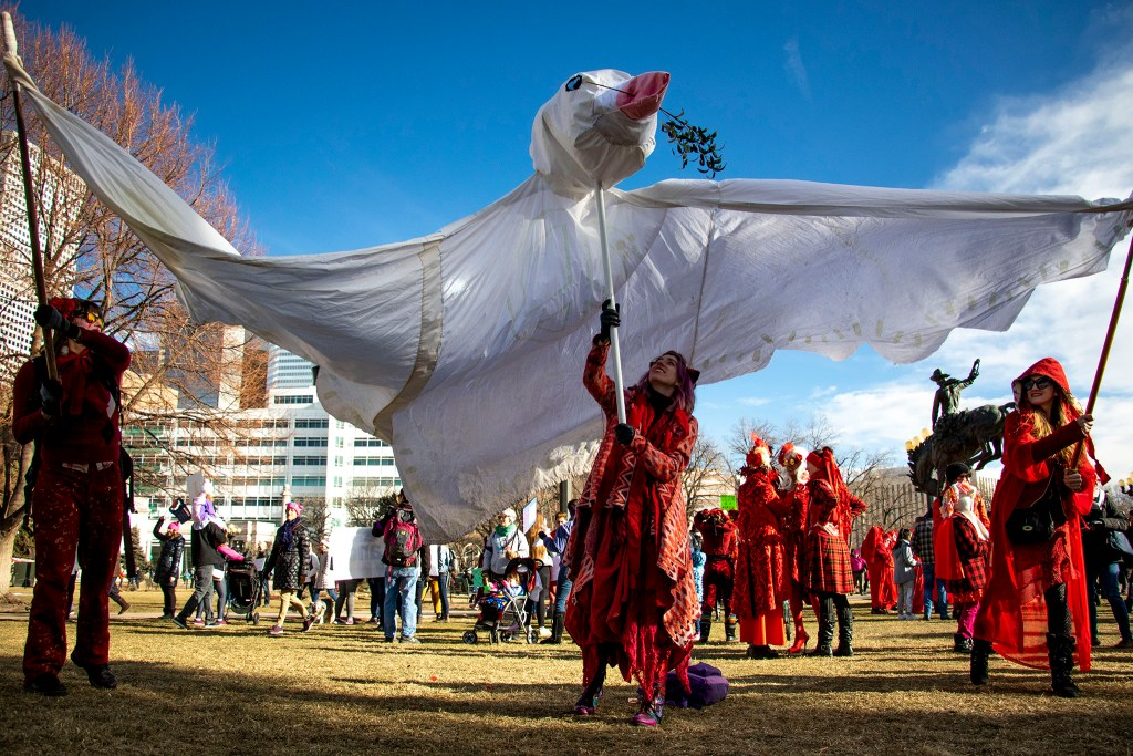 Rose Ashes (left to right), Khiri Lee and Brooke Sparling hold up a giant dove puppet before the Denver Womxn's March, Jan. 18, 2020. (Kevin J. Beaty/Denverite)