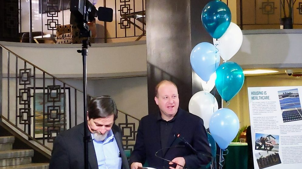John Parvensky, president and CEO of the Colorado Coalition for the Homeless on left, with Gov. Jared Polis on Jan. 21, 2020 at Fusion Studios, an old Quebec Street hotel that the Colorado Coalition for the Homeless has converted to housing for people who have experienced homelessness. (Donna Bryson/Denverite)