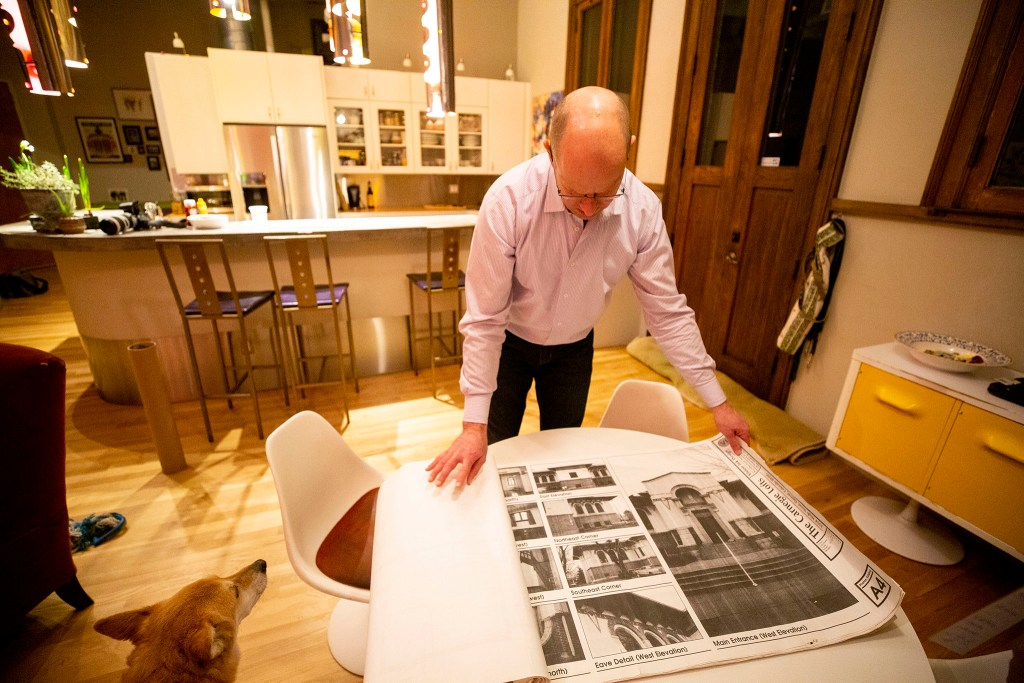 Keith Parks displays blueprints of his apartment, which was once a Carnegie library in Denver's Cole neighborhood. Feb. 5, 2020. (Kevin J. Beaty/Denverite)