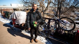 Isaac Finley poses for a portrait with his stuff, which he packed up after Denver officials warned he would be ticketed or arrested if he stayed camped here along the Sand Creek, right on the line between Denver and Commerce City. Feb. 5, 2020. (Kevin J. Beaty/Denverite)