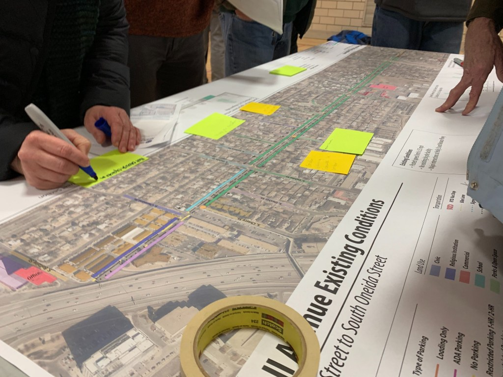 Residents write notes on a print out showing a proposed bike lane along Jewell Avenue during a meeting on Tuesday, Feb. 4, in southeast Denver. (Esteban L. Hernandez/Denverite)