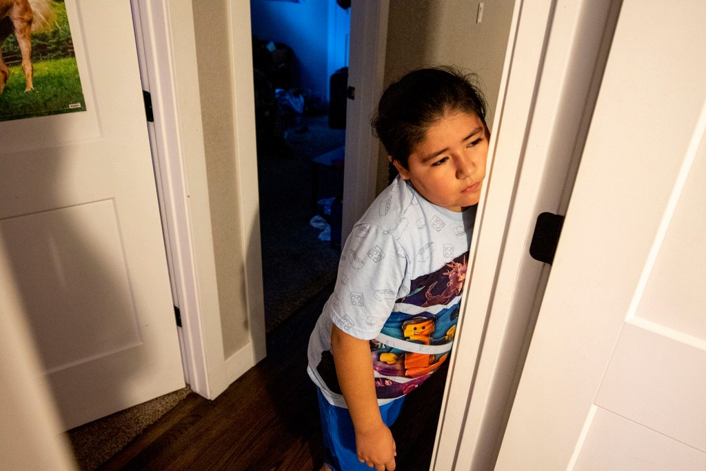 Francysco Zaldivar watches his mother pack her belongings for a long trip to Mexico, March 8, 2020. (Kevin J. Beaty/Denverite)