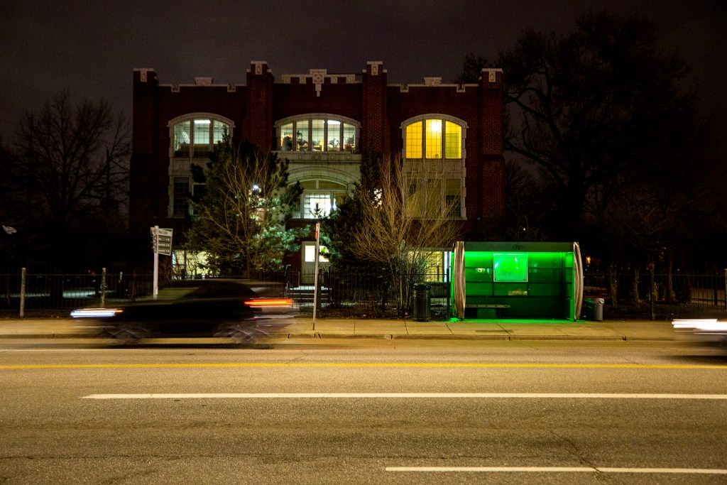 A solar-powered bus shelter is illuminated in Jolly Rancher green. West Colfax Avenue, March 12, 2020. (Kevin J. Beaty/Denverite)