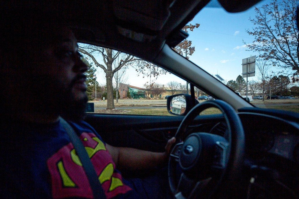 Julian Rai drives past the Colorado health department site where COVID-19 drive-through tests were administered just days before. March 13, 2020. (Kevin J. Beaty/Denverite)