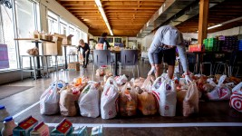 Alex Chavarria organizes groceries inside the Sun Valley Kitchen, March 25, 2020. (Kevin J. Beaty/Denverite)