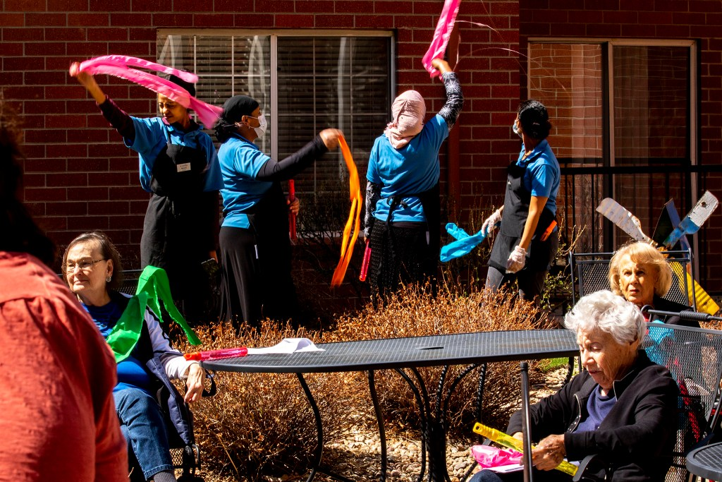 Residents and staff at the Springbrooke Senior Living center sing and dance in the courtyard. Washington Virginia Vale, March 27, 2020. (Kevin J. Beaty/Denverite)