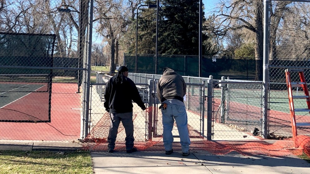 Crews put up netting at the City Park tennis courts in response to the COVID-19 pandemic. (David Sachs/Denverite)