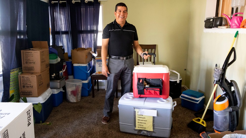 Jesus Velazquez poses for a portrait in his home with his burrito coolers, March 31, 2020. (Kevin J. Beaty/Denverite)